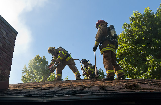Ross Valley Firefighters ventilate a roof at an early morning structure fire in Sleepy Hollow.  Photo by Todd Lando.